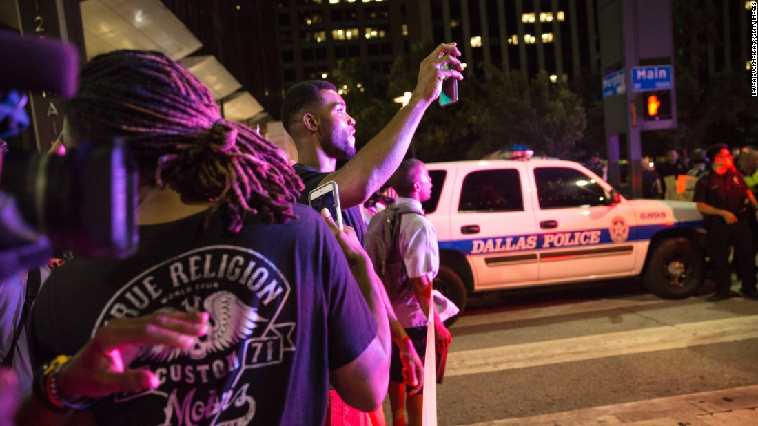 Onlookers stand near police barricades after the shootings.