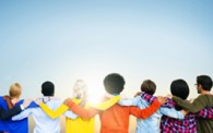 7 people with arms around each other's shoulders and backs facing the camera. Looking into the sunset with a blue sky above.