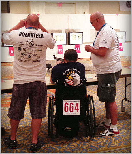 Photo of Veteran and Volunteers participating in an air rifle event