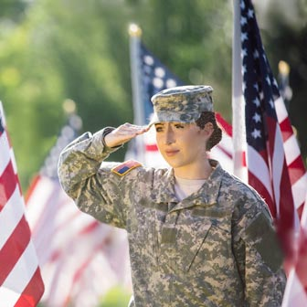 Female soldier in Army camouflage uniform, saluting the American flag