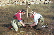Two crewmembers sampling invertebrates with a Slack sampler.