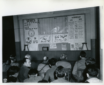 Original Caption: Officers and enlisted men of the 2nd Inf. Div., 1st U.S. Army, watch the board giving them the play-by-play description of the Army-Navy football game at their headquarters in Vith, Belgium. December 2, 1944. Local ID: 111-SC-197341
