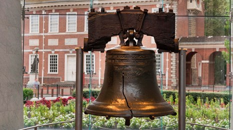 Color photo of the Liberty Bell with Independence Hall visible through the glass behind it.