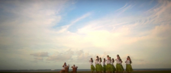 A hula halau performs under a beautiful sky with ethereal clouds overhead