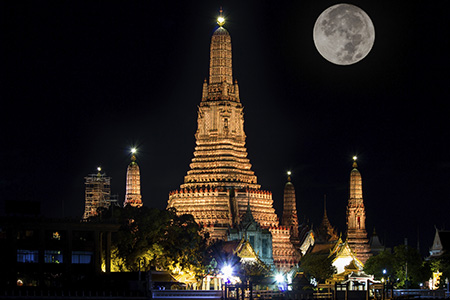 Temple by the river with full moon in night skies