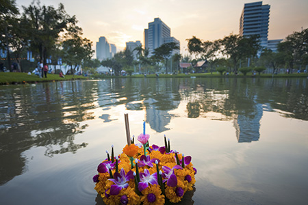 Krathong floating in the lake with buildings in the the reflection on the water