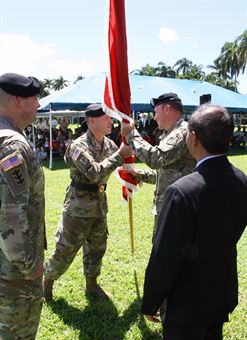 Lt. Col. James D. Hoyman (back right) receives the unit colors from former Pacific Ocean Division Commander Brig. Gen. Jeffrey L. Milhorn, becoming the 70th Commander of the U.S. Army Corps of Engineers Honolulu District. Looking on are outgoing District Commander Lt. Col. Christopher W. Crary (front left) and Acting Honolulu District Deputy District Engineer for Programs and Project Management Stephen Cayetano. Milhorn presided over the ceremony on the Palm Circle Parade Field at Fort Shafter.
