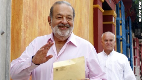 Mexican billionaire Carlos Slim (L) walks in a street of Cartagena de Indias, Colombia, on October 26, 2012. Colombian lawmakers on Wednesday asked Slim to appear before Congress over claims his telecommunications empire has abused its dominant position in the country. Lawmakers are seeking testimony from Slim, the world's richest man, to bring 'greater transparency' to the telecoms sector in Colombia, according to a copy of the correspondence inviting him to testify. AFP