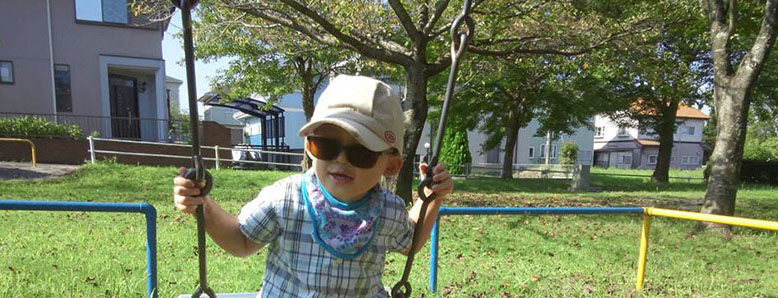 A child who has a rare disease playing on a swing