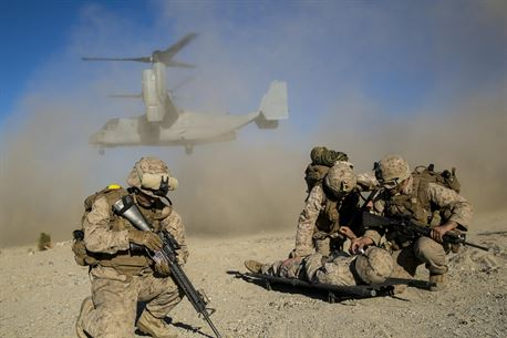 U.S. Marines with Battalion Landing Team 2/1, 13th Marine Expeditionary Unit (MEU), shield a simulated casualty from the debris of a U.S. Marine Corps MV-22 Osprey during Composite Training Unit Exercise (COMPTUEX) at  Marine Corps Air Ground Combat Center Twentynine Palms, California, Oct. 30, 2015. COMPTUEX provides the MEU ARG the opportunity to integrate naval training while also allowing focused, mission-specific training and evaluation for the Marines and their Navy counter parts. (U.S. Marine Corps photo by Cpl. Briauna Birl/RELEASED)