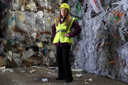 woman standing in front of recyclable material