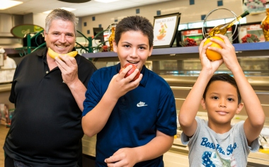 image of a man and two boys holding a piece of fruit