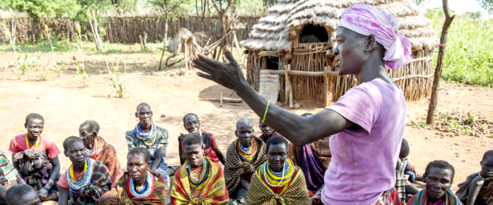 A women speaks to a group of villagers in a rural setting.