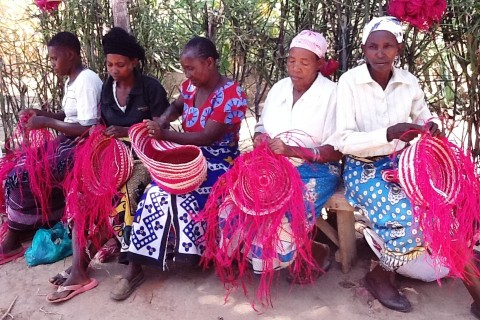 Women weavers in Kitui, Kenya constructing baskets destined for Walmart.