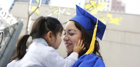Smiling Mother in graduation gown holding Daughter