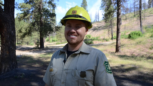 Photo of an employees standing in a wooded area in a uniform and a hard hat.
