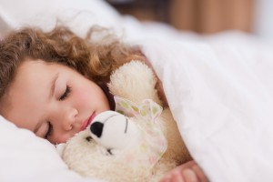 Little girl sleeping with a teddy bear.