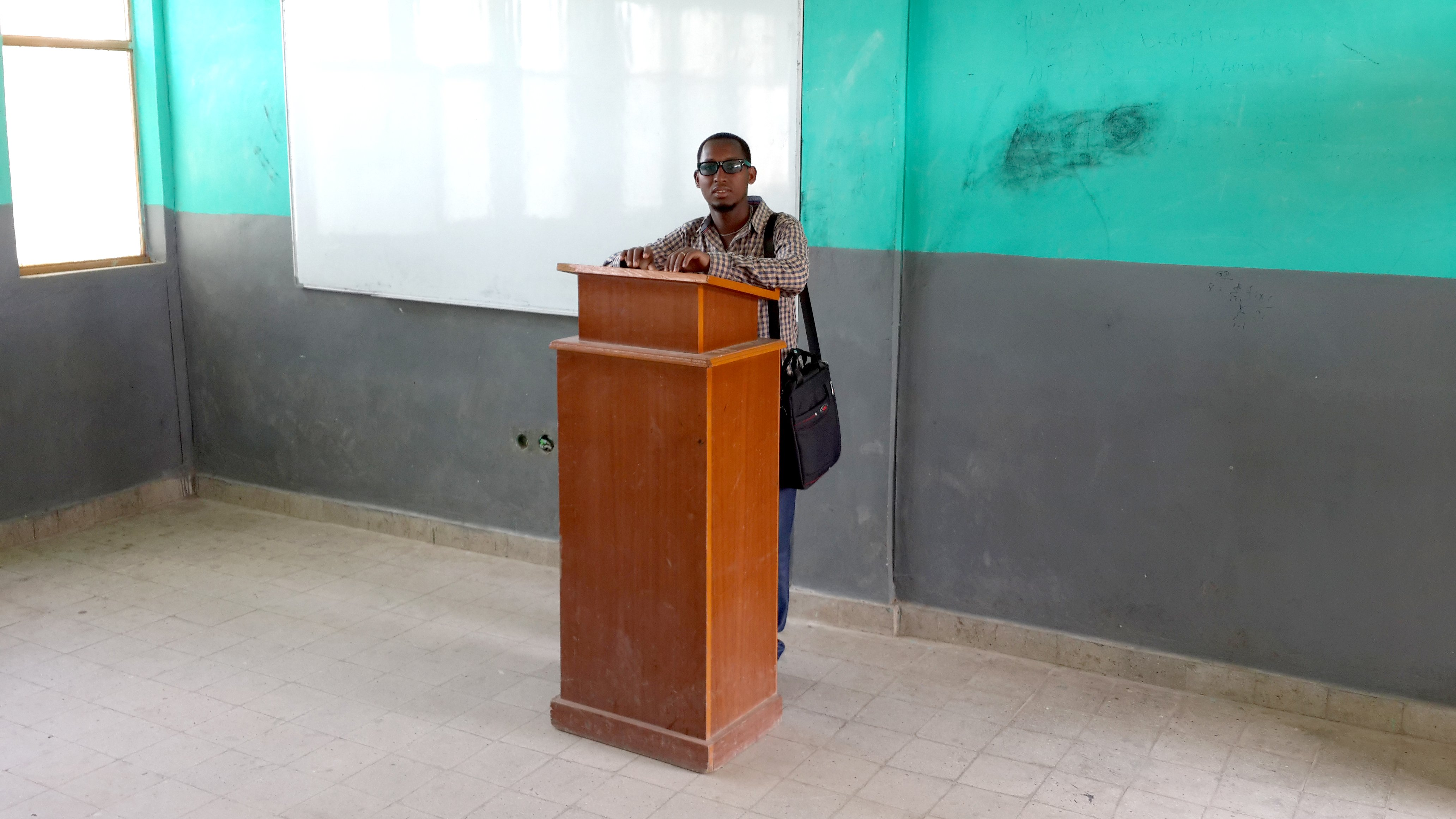 Young man stands at podium in front of class