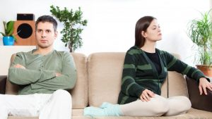 man-with-arms-crossed-on-couch-near-woman