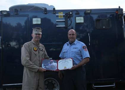 Lt. Col. Shaun T. Fitzpatrick, executive officer for Chemical Biological Incident Response Force, CBIRF, and Initial Response Force, IRF B, mission commander, presents a certificate of appreciation to Fire Capt. Michael Smithwick for his work in support of CBIRF during the training exercise with the Fire Department of New York, FDNY, on Randall's Island, N.Y., Sept. 15, 2016. CBIRF's Marines and sailors participated in a training event that included three days of lane training with FDNY instructors teaching classes in vehicle extrication, breaching, rope rescue and medical as part of urban rescue operations, and a final training operation in which CBIRF responded to a notional steam plant explosion. (Official U.S. Marine Corps photo by Lance Cpl. Maverick S. Mejia/RELEASED)
