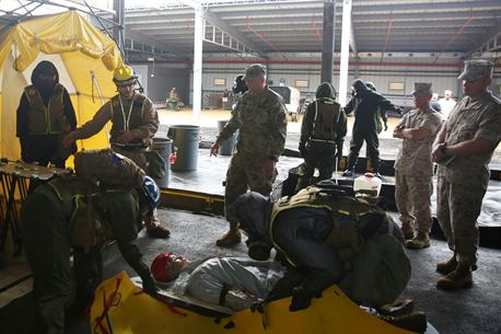 Marine Sgt. Sawyer Guerin, a team leader with Decontamination Platoon, Chemical Biological Incident Response Force (CBIRF), explains to Army Maj. Gen. Richard Gallant, commander of Joint Task Force Civil Support, how CBIRF Marines take casualties through non-ambulatory decontamination while other Marines demonstrate that process during an official visit at Naval Annex Stump Neck, Md., Sept. 29, 2016. Gallant visited CBIRF's own training site the Downey Responder Training Facility to learn more about the Marines and sailors with CBIRF, their training capabilities,  and the equipment they use for chemical, biological, radiological, nuclear and high-yield explosive (CBRNE) crisis response and consequence management. (Official U.S. Marine Corps photo by Sgt. Jonathan Herrera/Released)