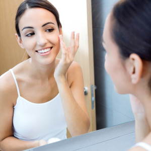 Portrait of young woman applying moisturizer cream on her pretty face in the bathroom