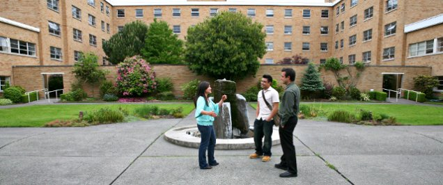 Three students talk in a courtyard.