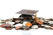A graduation cap is pictured atop a pile of coins.