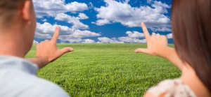 Couple Framing Hands Around Space in Grass Field and Sky on the Horizon.