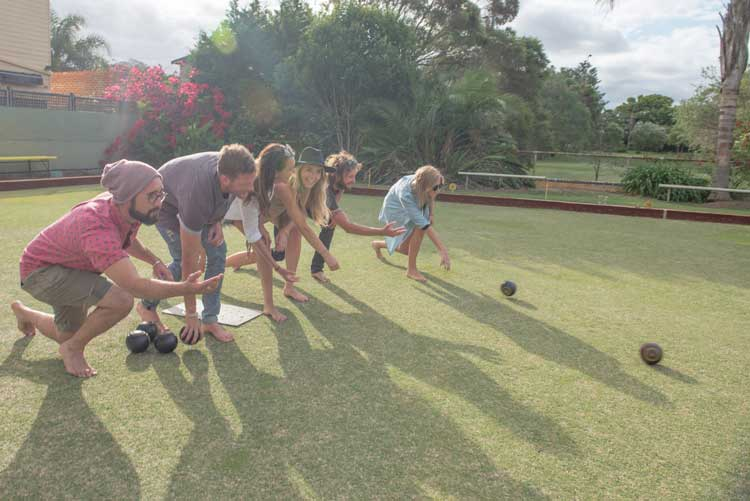 group of friends playing lawn bowls