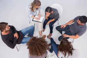 Therapist listening to patient during caduceus group therapy session