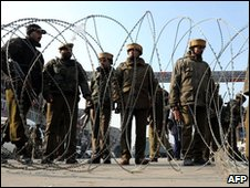 Indian police officials stand behind barbed wire blocking a road during a gunbattle in Srinagar - January 2010
