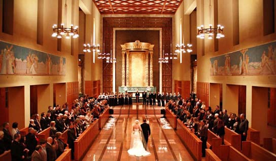 A bride and a groom walk down the aisle of Bastyr Chapel.