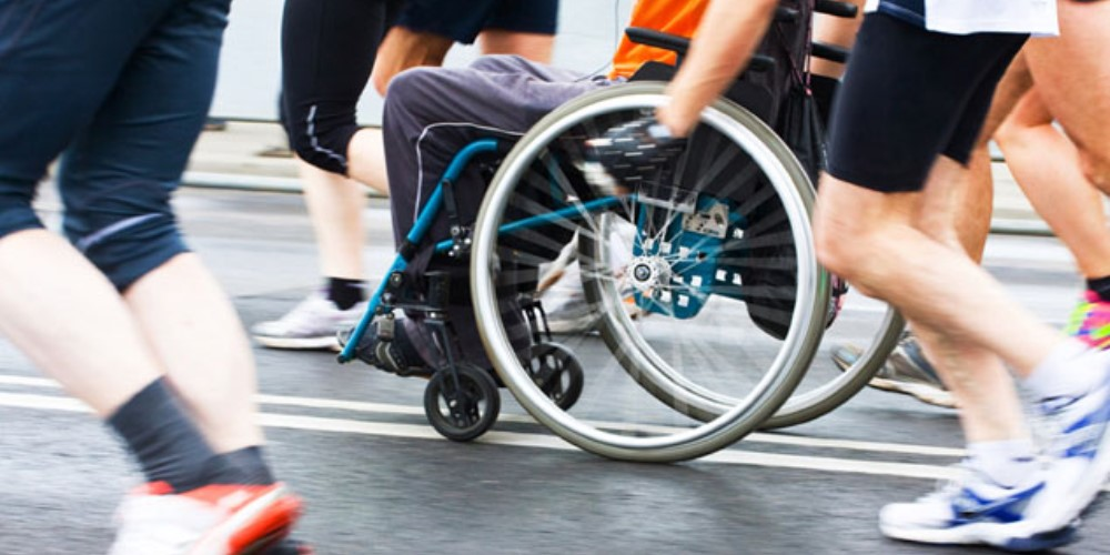 Runners and a wheelchair user taking part in an event