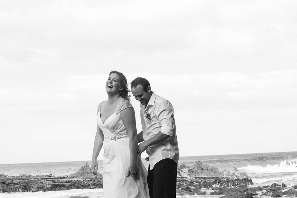 Black and white photo of a bride and groom at the beach cracking up laughing