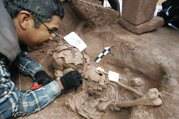 An archaeologist cleaning a human skeleton at a site in Tiwanaku, Bolivia.