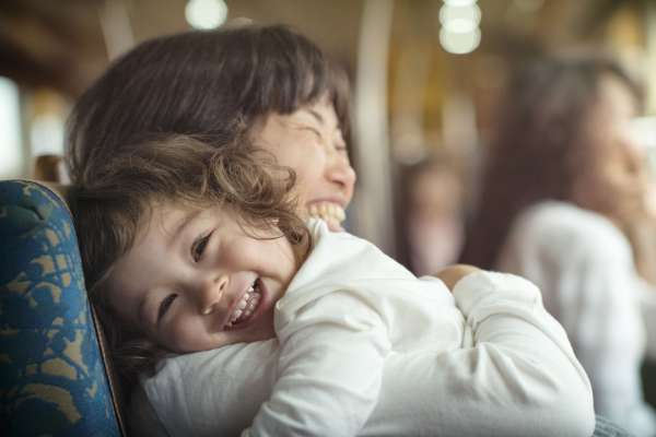 One year old girl gives her mom a big happy hug on a train ride to Ibusuki, Japan.