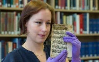 Erika Delbecque holding one of two pages of a 15th century printed text by English printer William Caxton
