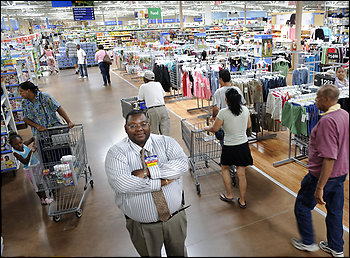 Wal-Mart is paying for newspaper advertising for businesses around its Landover Hills store, which is managed by Emanuel Gilliam, center.