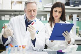 Zwei Wissenschaftler arbeiten gemeinsam im Labor und werten Proben aus.