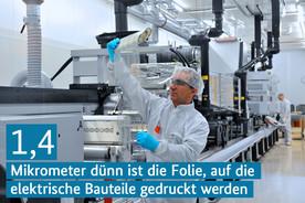 Ein Mann steht in einer Fabrikhalle und prüft eine bedruckte Folie.