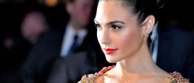 Israeli actress Gal Gadot wearing a sequined coral dress with her hair in a chignon staring off to the side as if on the red carpet