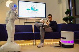 Das Bild zeigt, einen Mann zu Hause mit zwei Servicerobotern.