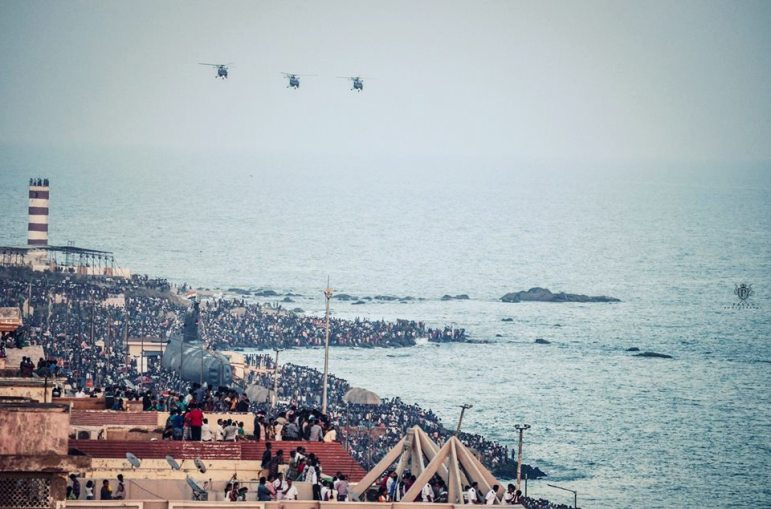 People watching navy day on beach