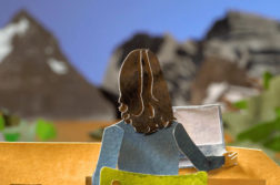 woman sitting at desk, facing Rocky Mountains