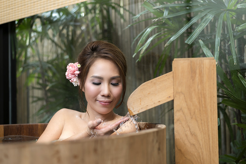 a Japanese woman enjoys a bath in a wooden deep soaker tub