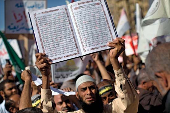 During a massive rally in Cairo's Tahrir Square on Nov.ember 9, 2012, in which conservative Muslims demanded that Shariʿah law provide the foundation for a new Egyptian constitution, a man holds the Qurʾan aloft.
