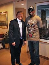 Donald Trump posing with former basketball player Dennis Rodman in a room with paintings adorning the walls. Trump is wearing a suit with a light-colored tie and dress shirt, while Rodman is wearing a brown T-shirt with a design on it, blue jeans, and a baseball cap that also has a design on it.