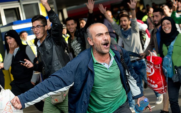 A man cheers as he and other refugees arrive at the main train station in Munich, Germany