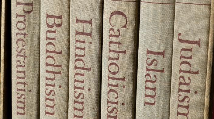 Books on a shelf with different titles on the spines: Judaism, Islam, Catholicism, Hinduism, Buddism, Protestantism